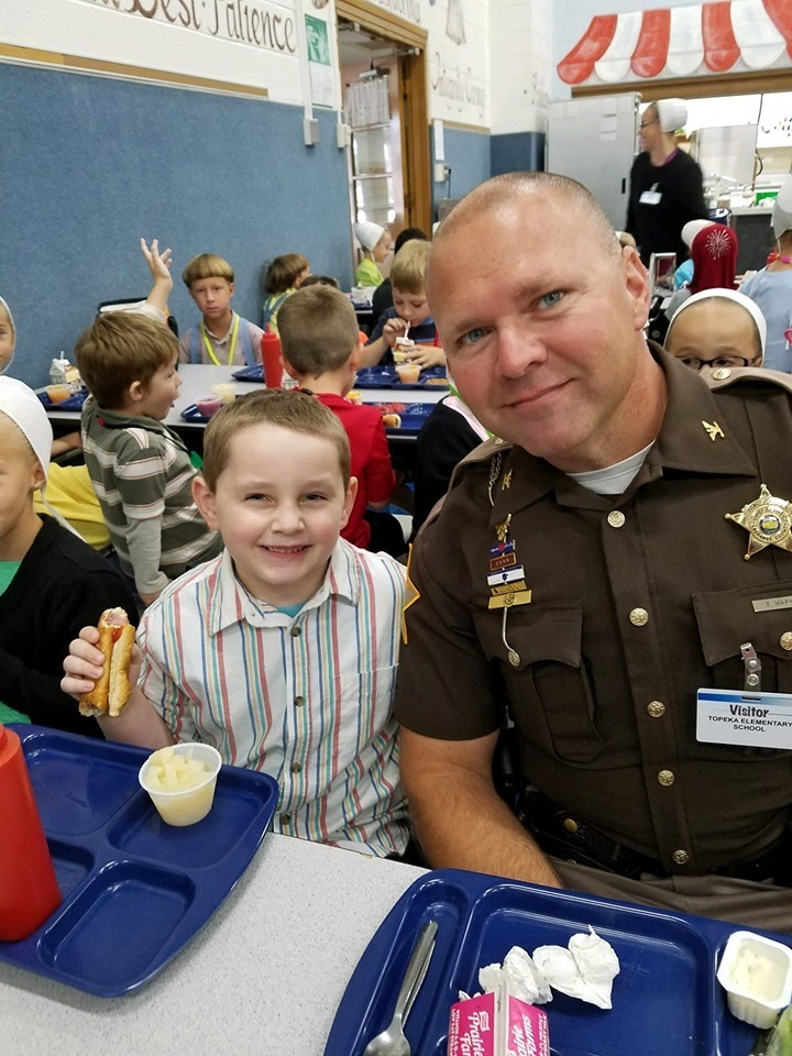 County officer eating lunch with student